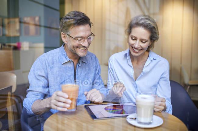Mujer feliz y hombre usando la tableta en un café - foto de stock