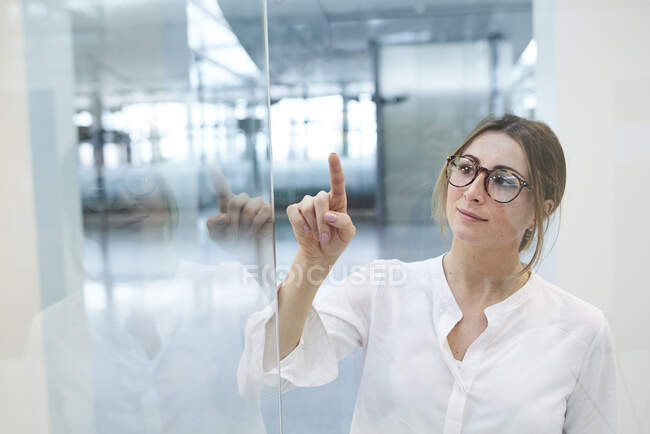 Young businesswoman touching virtual touchscreen — Stock Photo