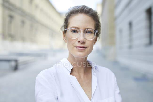 Retrato de mujer confiada con gafas y camisa blanca en la ciudad - foto de stock