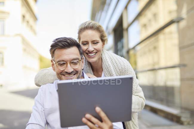 Pareja feliz usando la tableta en la ciudad - foto de stock