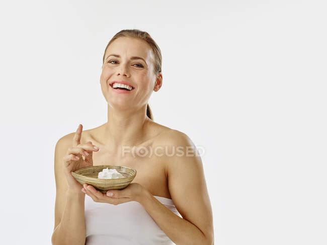 Mujer joven aplicando crema corporal, crema en un tazón - foto de stock