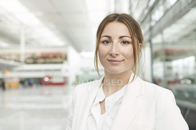 Retrato de una joven empresaria sonriente en el aeropuerto - foto de stock