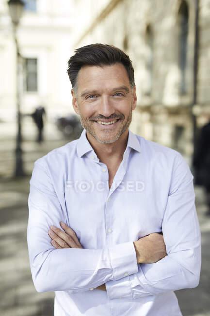 Retrato de un hombre de negocios sonriente en la ciudad - foto de stock