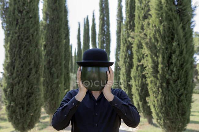 Italia, Toscana, hombre rodeado de cipreses con un sombrero de jugador de bolos sosteniendo un melón - foto de stock