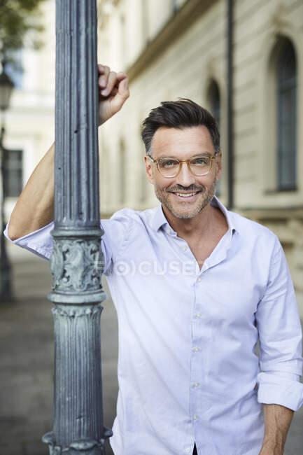 Retrato del hombre de negocios sonriente apoyado contra el poste de la lámpara en la ciudad - foto de stock