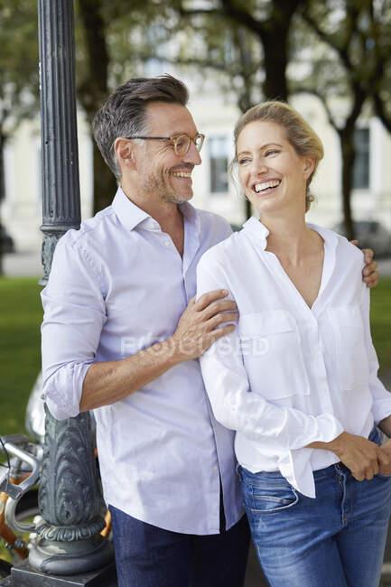 Pareja feliz abrazándose en la ciudad - foto de stock