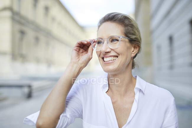 Retrato de una mujer sonriente con camisa blanca y gafas en la ciudad - foto de stock