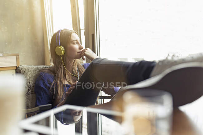 Relaxed young woman sitting on a chair wearing headphones — Stock Photo