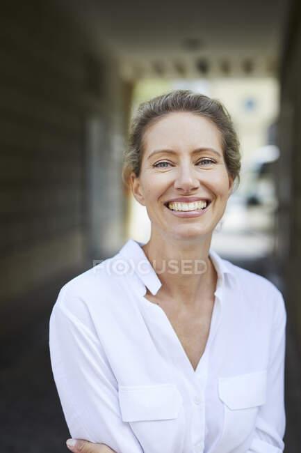 Retrato de mujer feliz vistiendo camisa blanca en la ciudad - foto de stock