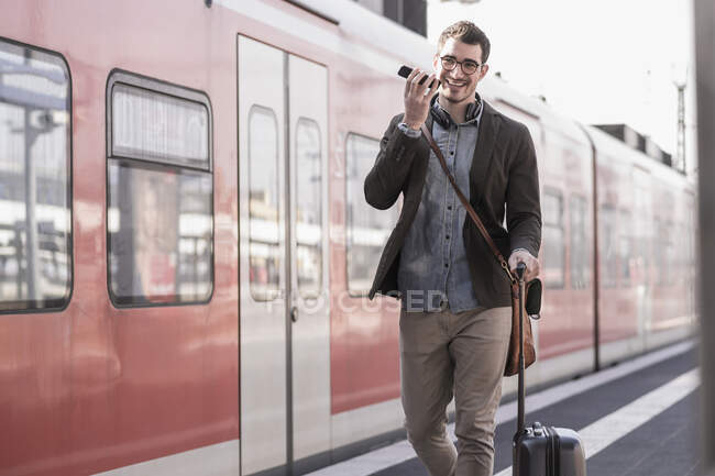 Happy young man with cell phone walking on station platform along commuter train — Stock Photo