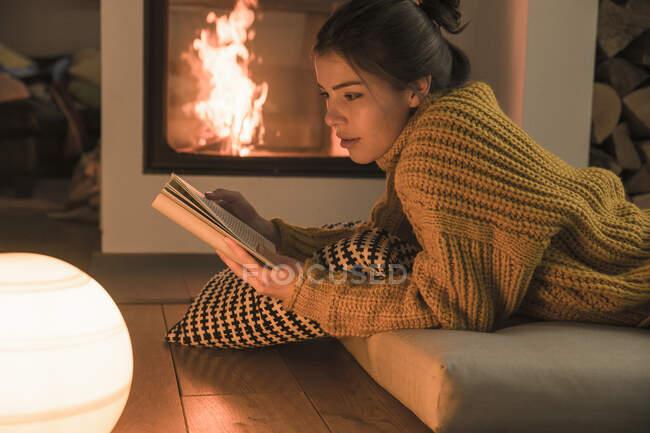 Junge Frau liest Buch am heimischen Kamin — Stockfoto