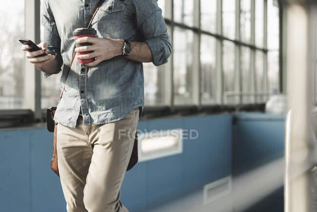 Крупный план человека с сотовым телефоном и кофе на вынос пешком на вокзале — стоковое фото
