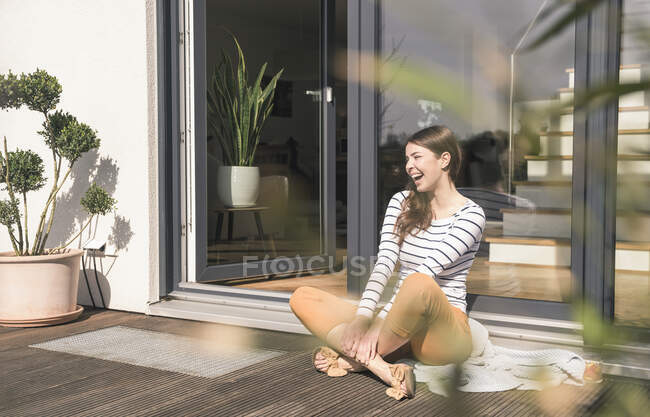 Laughing young woman sitting on terrace at home — Stock Photo