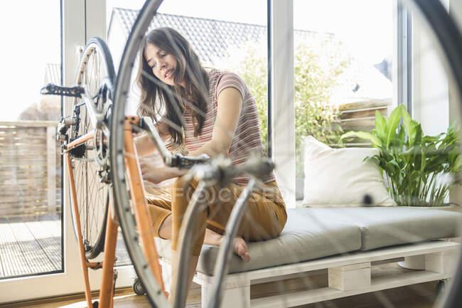 Молода жінка ремонтує велосипед вдома. — стокове фото