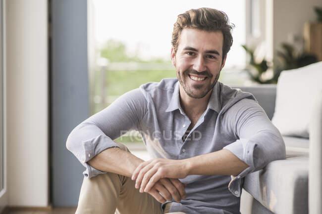 Portrait de jeune homme assis dans son salon — Photo de stock