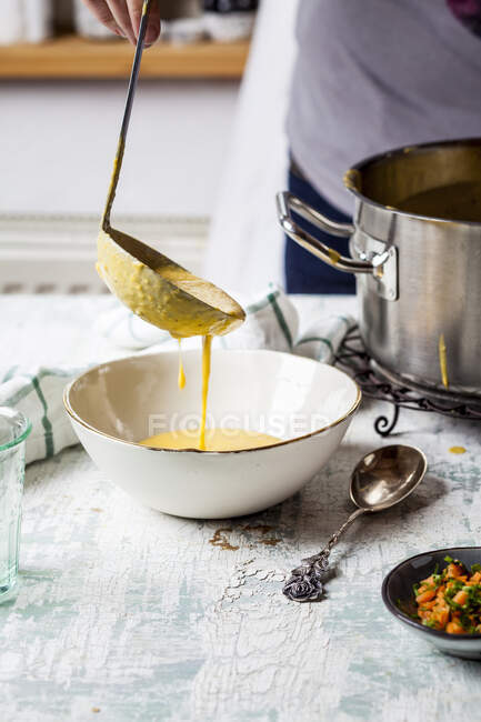 Woman pouring creme of carrot soup into a bowl, partial view — Stock Photo