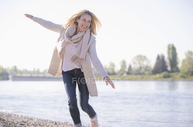 Carefree mature woman at the riverside — Stock Photo
