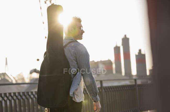 Joven con estuche de guitarra en la ciudad al atardecer - foto de stock