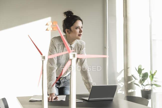 Деловая женщина с моделями ветряных турбин и ноутбуком на столе в офисе — стоковое фото