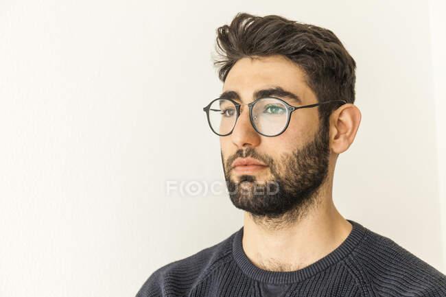 Retrato de un joven pensativo con barba y gafas - foto de stock