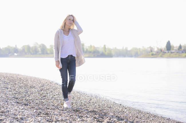 Зрелая женщина, идущая по берегу реки — стоковое фото