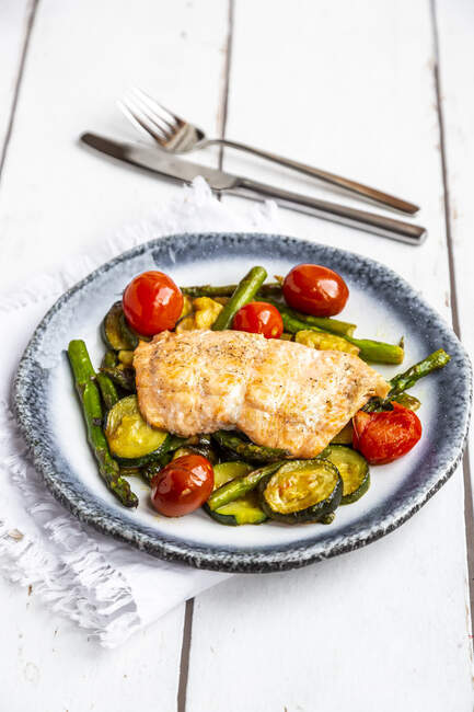 Coalfish fillet on zucchini, green asparagus and tomato, low carb — Stock Photo