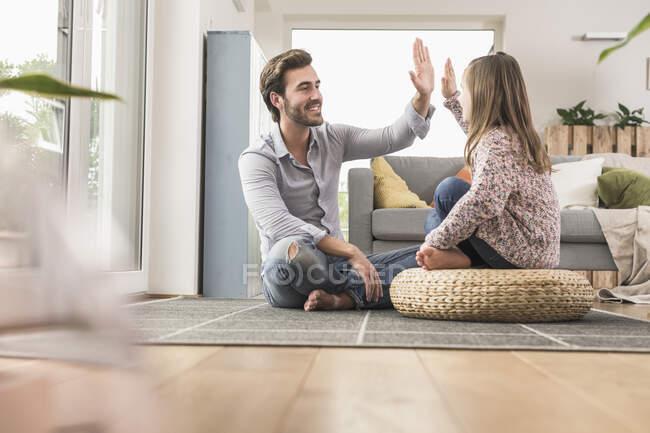 Молодой человек и маленькая девочка сидят дома и дают пять — стоковое фото