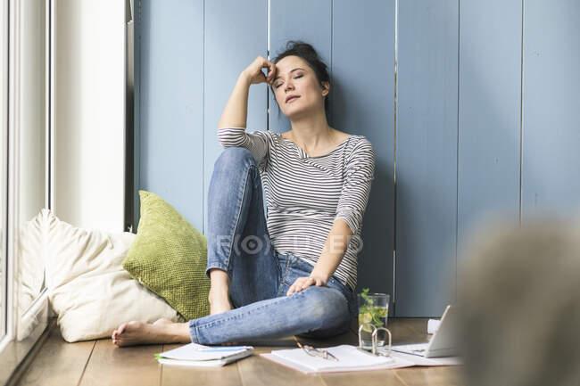 Donna rilassata seduta alla finestra a casa a fare una pausa — Foto stock