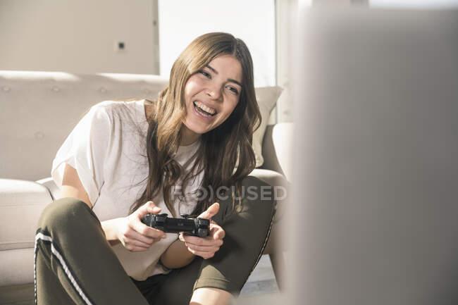 Счастливая молодая женщина играет в видеоигры дома — стоковое фото