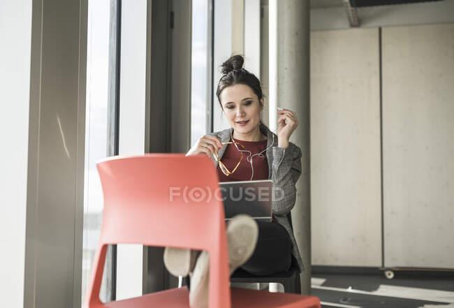 Femme d'affaires assis sur la chaise dans le bureau avec ordinateur portable et écouteurs — Photo de stock