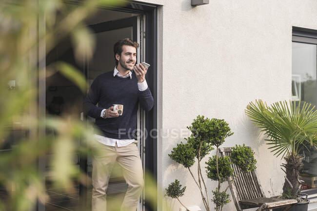 Junger Mann lehnt an Tür seines Hauses, hält Tasse Kaffee, benutzt Smartphone — Stockfoto