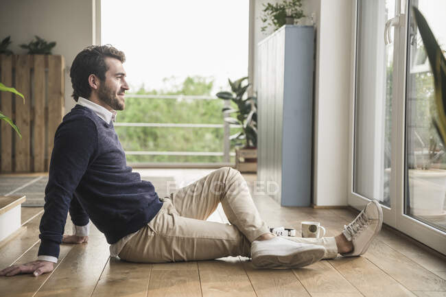 Young man sitting on floor, looking out of window, relaxing — Stock Photo