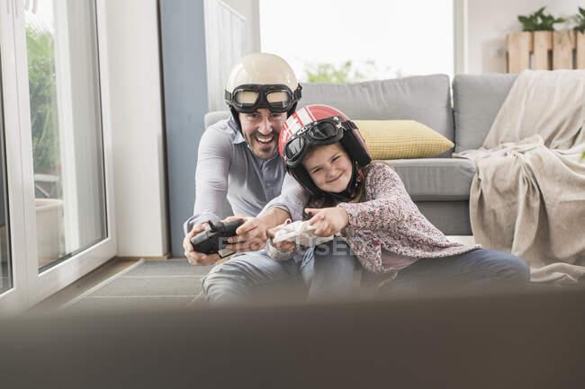 Молодой человек и маленькая девочка в байкерских шлемах, играют в гоночные игры с игровыми консолями — стоковое фото
