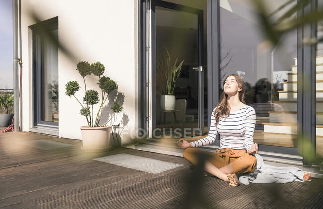 Young woman sitting on terrace at home practicing yoga — Stock Photo