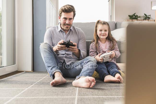 Joven hombre y niña jugando juego de ordenador con consola de juegos - foto de stock