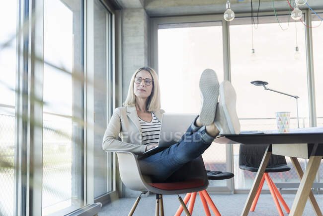 Расслабленная деловая женщина с ноутбуком в офисе с поднятыми ногами — стоковое фото