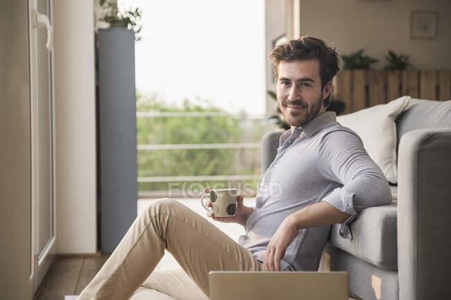 Junger Mann sitzt zu Hause auf dem Fußboden, benutzt Laptop, trinkt Kaffee — Stockfoto