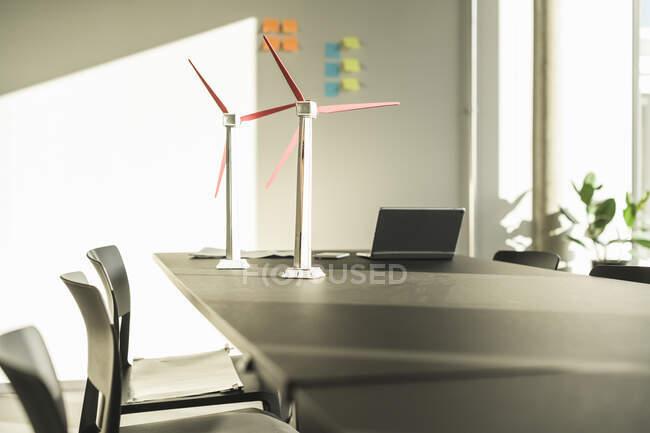 Модели ветряных турбин и ноутбук на столе в офисе — стоковое фото