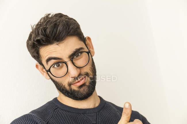 Retrato de joven incrédulo con barba y gafas - foto de stock