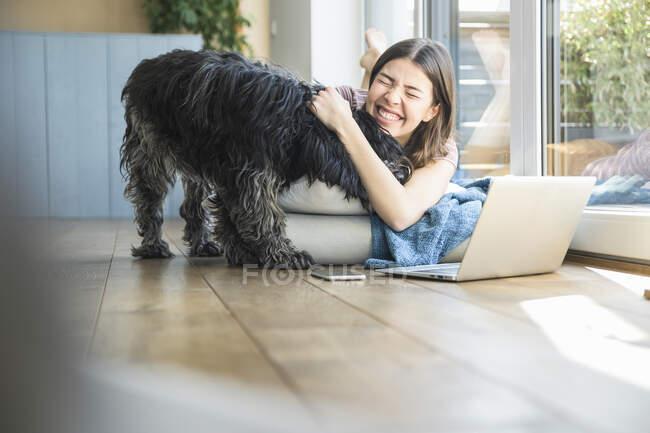 Щаслива молода жінка з собакою лежить біля вікна. — стокове фото