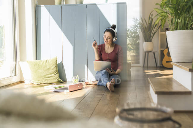 Mujer con auriculares sentados en la ventana en casa usando portátil - foto de stock