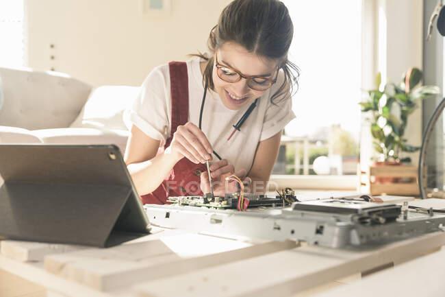 Молодая женщина работает на компьютерном оборудовании дома рядом с планшетом — стоковое фото