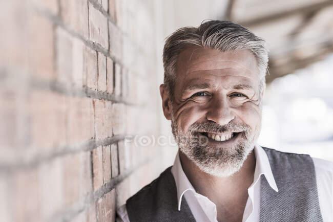 Retrato de homem de negócios maduro sorridente encostado a uma parede de tijolo — Fotografia de Stock
