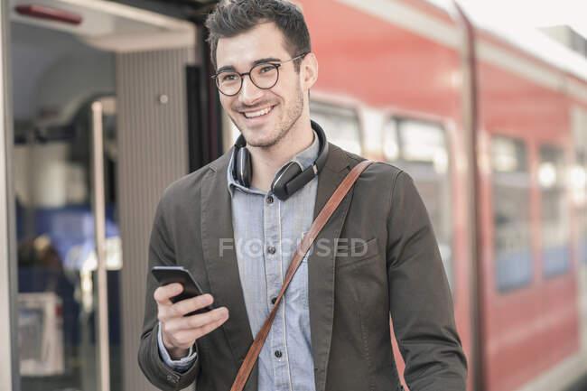 Улыбающийся молодой человек с сотовым телефоном на пригородном поезде — стоковое фото