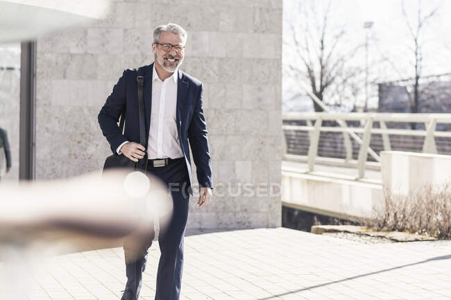 Smiling mature businessman on the move in the city — Stock Photo
