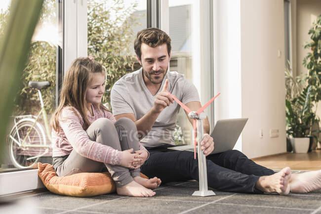 Joven y niña jugando con el modelo de un aerogenerador - foto de stock