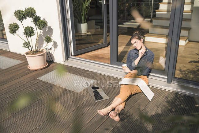 Young woman sitting on terrace at home working with book and laptop — Stock Photo