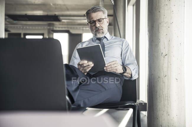 Homme d'affaires mature assis sur une chaise en utilisant une tablette — Photo de stock