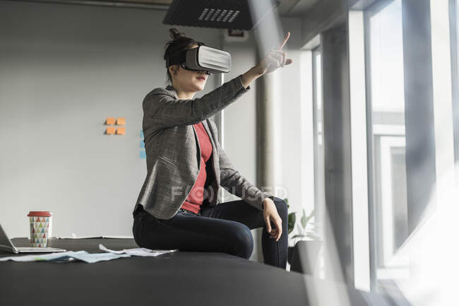 Businesswoman sitting on desk in office wearing VR glasses — Stock Photo
