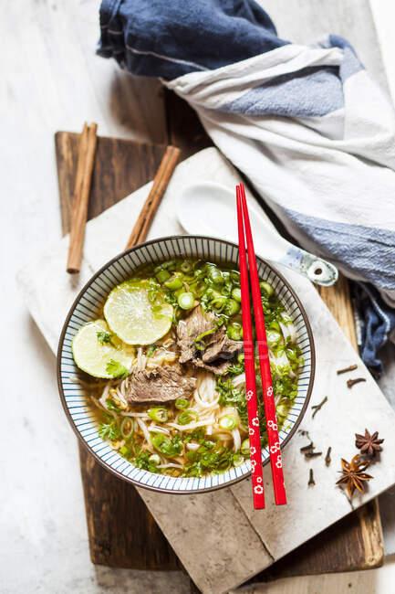 Cuenco de Pho vietnamita con fideos de arroz, frijoles mungo, cilantro, cebolletas y limas - foto de stock